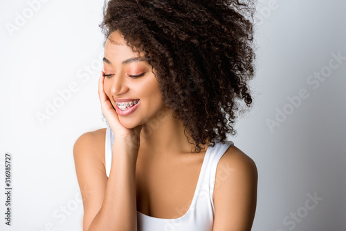 smiling curly african american girl with dental braces, isolated on grey