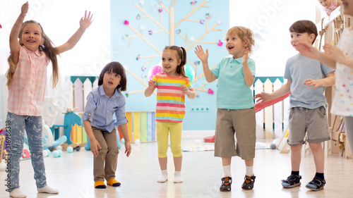 Cheerful kids stand semicircle on floor in kindergarten or daycare centre. Preschoolers have fun indoors, playing games - 316986318
