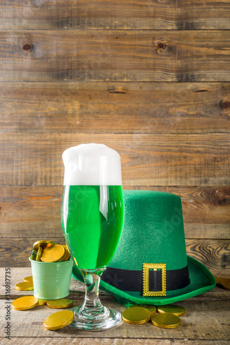 Fototapeta Traditional irish alcohol for St Patrick's day party. Different glasses with green beer, with golden chocolate coins decor and green leprechaun hat. Old rustic wooden background copy space obraz