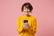 canvas print picture - Cheerful young brunette woman girl in yellow sweater posing isolated on pastel pink wall background studio portait. People lifestyle concept. Mock up copy space. Using mobile phone typing sms message.