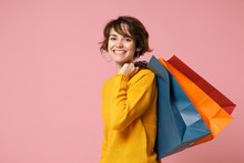 Cheerful Young Brunette Woman Girl In Yellow Sweater Posing Isolated On Pink Wall Background In Studio. People Lifestyle Concept. Mock Up Copy Space. Holding Package Bag With Purchases After Shopping.