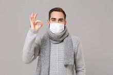 Young Man In Gray Sweater, Scarf Isolated On Grey Background. Healthy Lifestyle, Ill Sick Disease Treatment, Cold Season Concept. Mock Up Copy Space. Wearing Sterile Face Mask, Showing OK Gesture.