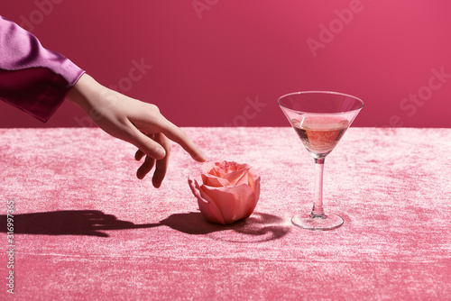 Fotografija cropped view of woman touching rose near glass with drink on velour cloth isolat