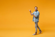 Excited Young Bearded Man In Casual Blue Shirt Posing Isolated On Yellow Orange Background Studio Portrait. People Sincere Emotions Lifestyle Concept. Mock Up Copy Space. Pointing Index Fingers Aside.