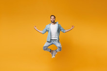 Smiling Young Bearded Man In Casual Blue Shirt Posing Isolated On Yellow Orange Wall Background. People Lifestyle Concept. Mock Up Copy Space. Jumping Hold Hands In Yoga Gesture, Relaxing Meditating.