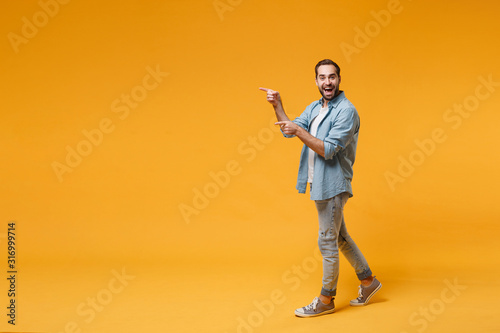Obraz Excited young bearded man in casual blue shirt posing isolated on yellow orange background studio portrait. People sincere emotions lifestyle concept. Mock up copy space. Pointing index fingers aside. - fototapety do salonu
