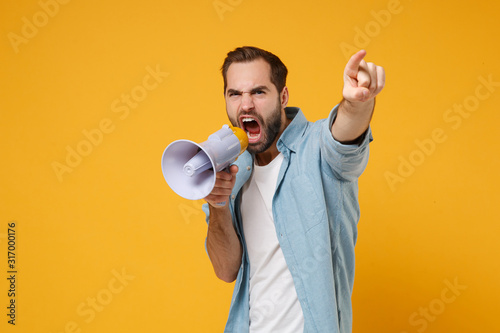 Fototapety, obrazy: Young man in casual blue shirt posing isolated on yellow orange background studio portrait. People sincere emotions lifestyle concept. Mock up copy space. Scream in megaphone point index finger aside.