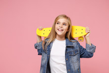 Charming Little Blonde Kid Girl 12-13 Years Old In Denim Jacket Posing Isolated On Pastel Pink Background Children Portrait. Childhood Lifestyle Concept. Mock Up Copy Space. Hold Yellow Skateboard.