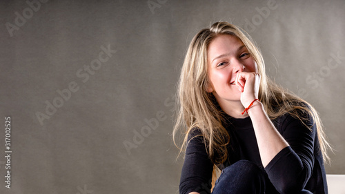naughty young blonde girl on a gray background, copy space Canvas