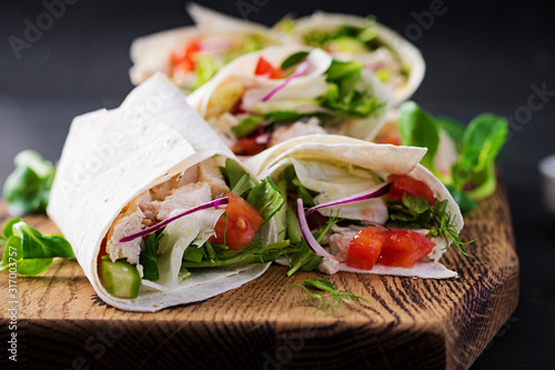 Fotografía Fresh tortilla wraps with chicken and fresh vegetables on wooden board