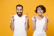 Young Couple Friends Bearded Guy Girl In White T-shirts Isolated On Yellow Orange Background. People Lifestyle Concept. Mock Up Copy Space. Wait For Special Moment Keeping Fingers Crossed Making Wish.
