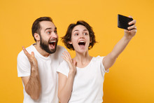 Excited Young Couple Friends Bearded Guy Girl In White T-shirts Isolated On Yellow Orange Background. People Lifestyle Concept. Mock Up Copy Space. Doing Selfie Shot On Mobile Phone, Spreading Hands.