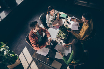 Top above high angle view of four busy experienced businesspeople in casual formal-wear discussing company finance report at modern industrial loft wood interior work place station