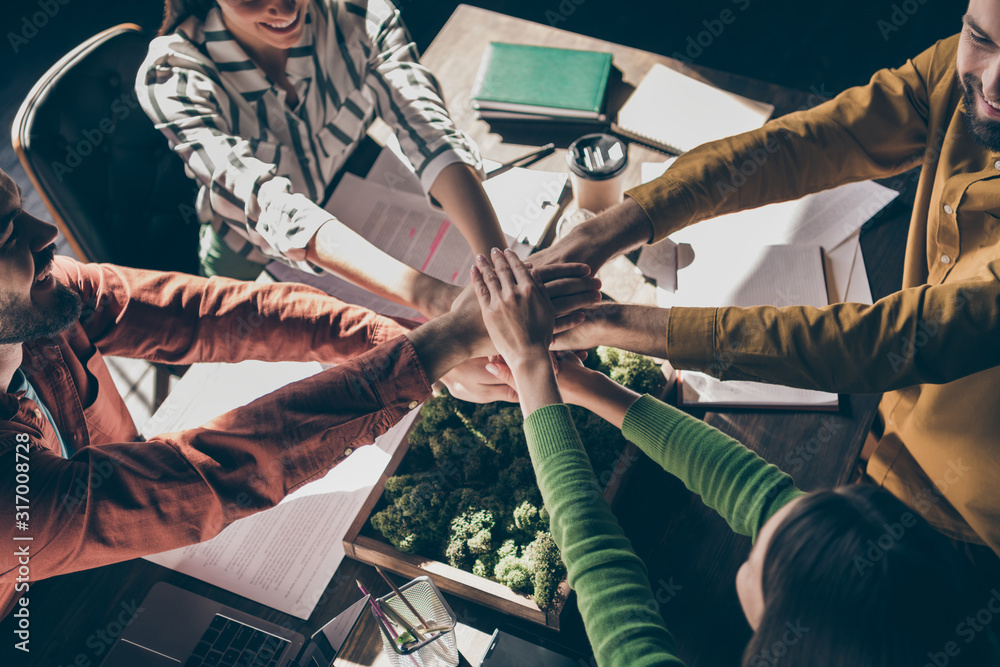 Fototapeta Cropped top above high angle view of four nice cheerful professional businesspeople wearing casual formalwear putting hands together over desk at modern interior workplace station