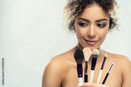 Beautiful woman with makeup brushes near her face - isolated on white Canvas Print