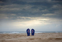 Australian Thongs Sticking Upright In Sand With Dramatic Storm Clouds Background. Australia Day And Waiting For Rain Concept.