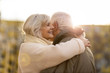 canvas print picture - Senior couple hugging outdoors in autumn