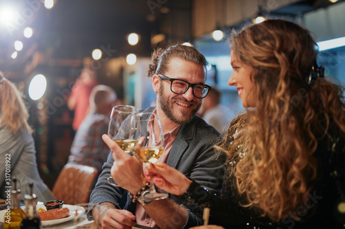 Fotomural Cute caucasian couple sitting in restaurant and cheering with wine
