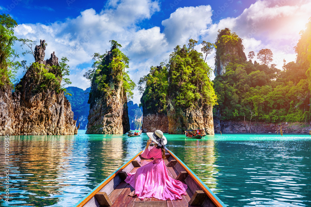 Fototapeta Beautiful girl sitting on the boat and looking to mountains in Ratchaprapha Dam at Khao Sok National Park, Surat Thani Province, Thailand.