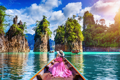 Obraz Beautiful girl sitting on the boat and looking to mountains in Ratchaprapha Dam at Khao Sok National Park, Surat Thani Province, Thailand. - fototapety do salonu