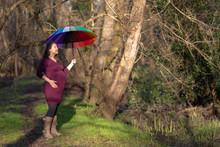 Pregnant Woman Holding A Colorful Umbrella
