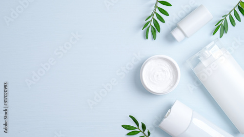 Fototapeta Natural organic cosmetic products concept. Hair care herbal cream in jar, shampoo bottle, shower gel container and green leaves. SPA cosmetic packaging branding mockup. Flat lay minimalist style set obraz
