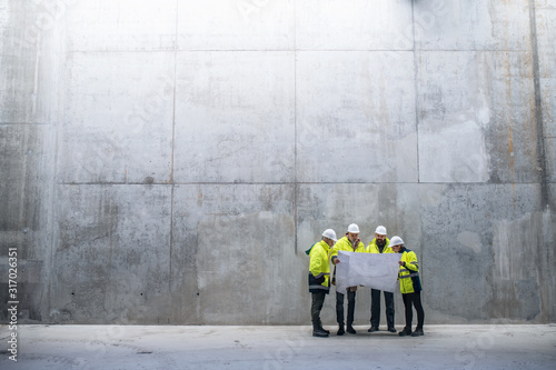 Fototapeta A group of engineers standing against concrete wall on construction site. obraz