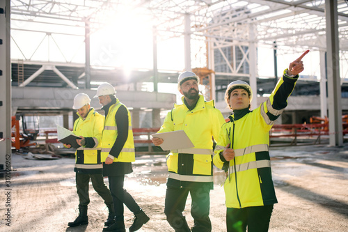 Obraz Group of engineers standing outdoors on construction site, working. - fototapety do salonu