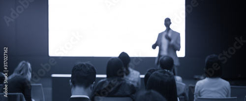 Speaker on the stage with rear view of audience in the conference hall or seminar meeting, business and education concept. Speaker giving a talk at business meeting. Seminar presentation photo. - 317027162