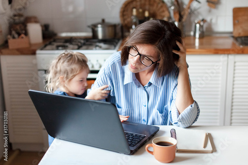 Obraz Working mother in home office. Unhappy woman and child using laptop. Sad and angry daughter needs attention from busy exhausted mom. Freelancer workplace in kitchen. Female business. Lifestyle moment. - fototapety do salonu