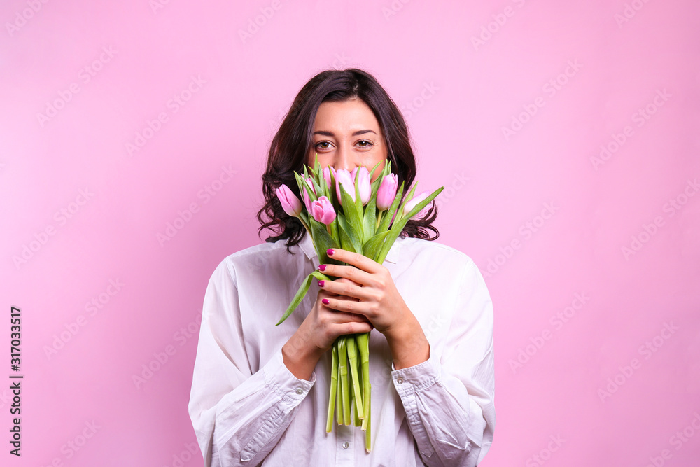 Fototapeta Studio portrait of gorgeous young brunette woman with long wavy hair wearing white loose cotton shirt, holding bouquet of tulip flowers. Pink isolated background, copy space, close up.