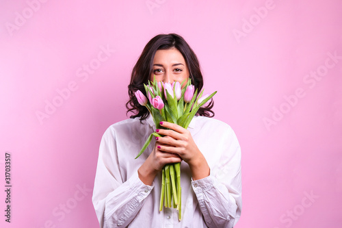 Obraz Studio portrait of gorgeous young brunette woman with long wavy hair wearing white loose cotton shirt, holding bouquet of tulip flowers. Pink isolated background, copy space, close up. - fototapety do salonu