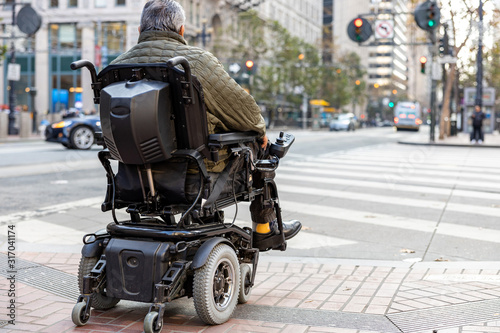 Obraz An elderly disabled person on an electric wheelchair on a city street in front of a pedestrian crossing. The concept of modern technology for people with disabilities. - fototapety do salonu