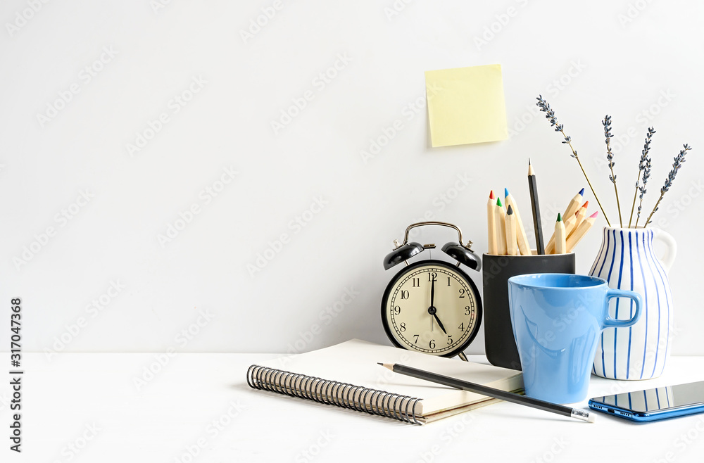 Fototapeta Office desk with notepad, pencils, coffee, clock on white table over white wall. Front view. Mockup