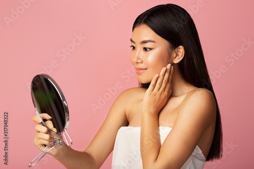 Personal care. Asian girl holding mirror and admiring herself Wallpaper Mural