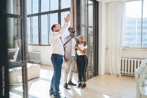 Professional estate agent showing apartment to African American amused couple