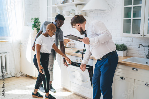 Foto Confident estate agent showing kitchen to African American thoughtful couple