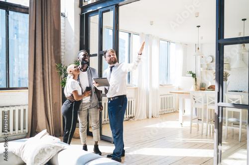 Fototapeta Multiethnic couple inspecting new apartment with estate agent obraz