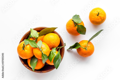 Ripe tangerines on white table. Citruses with green leaves in bowl top-down