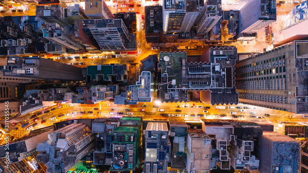 Fototapeta Aerial top view of downtown district  buildings in night city light. Bird's eye view from drone of cityscape metropolis skyline, crossing streets with parked cars. Development infrastructure