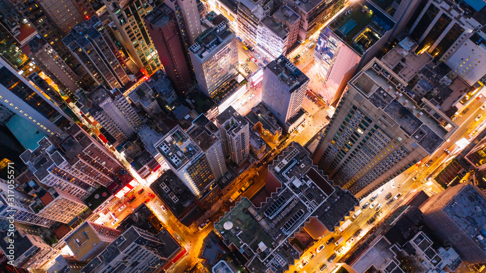 Fototapeta Aerial top view of downtown district  buildings in night city light. Bird's eye view from drone of cityscape metropolis infrastructure, crossing streets with parked cars. Development infrastructure