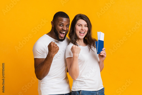 Obraz Overjoyed interracial couple holding passports with flying tickets, celebrating getting visa - fototapety do salonu