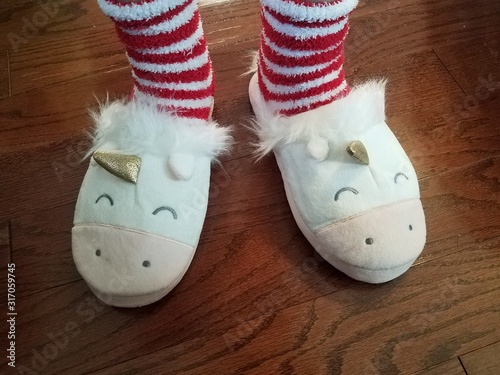 red and white socks with unicorn slippers on floor