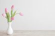 canvas print picture - pink tulips in white ceramic vase on wooden table on background white wall