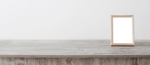 Wooden Frame On Wooden Table On Background White Wall