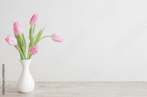 Obraz pink tulips in white ceramic vase on wooden table on background white wall - fototapety do salonu