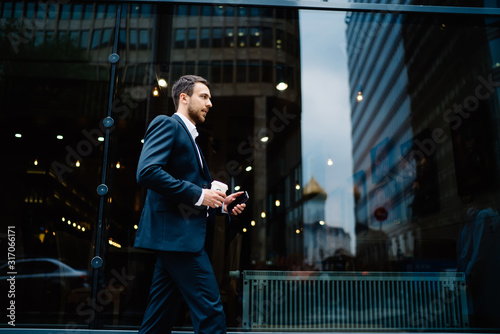 Serious businessman rushing to work with smartphone and coffee in street in downtown