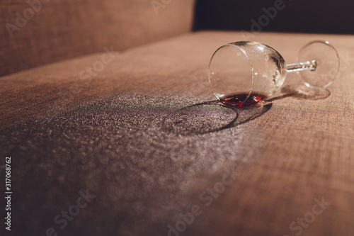 Red wine spilled on a brown couch sofa. Wallpaper Mural