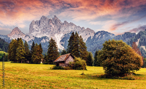 Obraz Awesome alpine highlands during sunset. Scenic image of fairy-tale Landscape with colorful sky and majestic Rock Mountain on background. Wild area. Amazing countryside in alps with traditional hut - fototapety do salonu