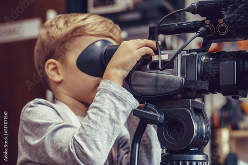 Little boy shooting video with camera in a studio. Wallpaper Mural